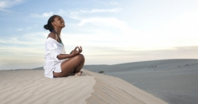 black woman meditating in desert smiling