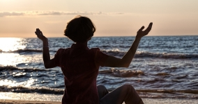Person with hands raised up by the sea shore at sunset