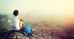 woman sitting on mountain looking at sunlit view