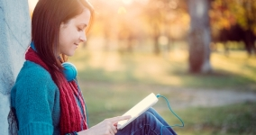 young woman sitting outdoors reading ebook
