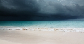 dark clouds over blue ocean and shore