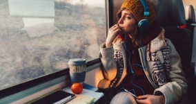girl on train wearing headphones and winter hat looking out the window