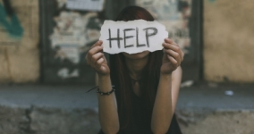 girl holding help sign