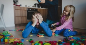 Kids play with toys scattered all over and tired exhausted parent