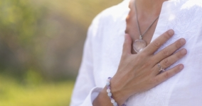woman in white shirt with hand on chest