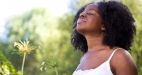 young black woman inhaling deeply outdoors with greenery in the background