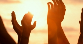 silouette of hands lifted to the sun