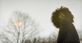 black woman with afro staring up and over her shoulder, bare tree in the background