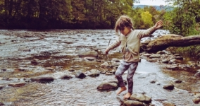 child playing in a stream