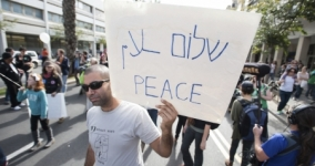 Person holding sign at a protest that reads shalom peace salaam