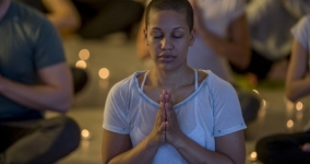 black woman with closely cropped hair meditating with candles in the background