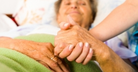 nurse holding old woman's hand