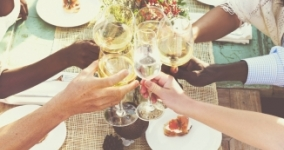 multiracial group of people clinking wine glasses at meal