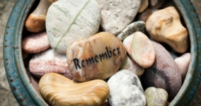 bowl of stones with one in the middle showing the word remember