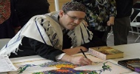 man wearing tallit and kippah signing a colorful ketubah