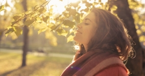 woman breathing outdoors with eyes closed in sunshine surround by trees