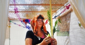woman holding lulav in sukkah
