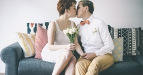 genderqueer couple dressed up and kissing with white flowers in hand