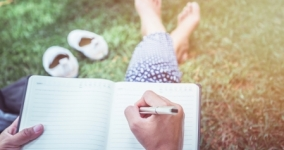 person sitting barefoot in grass writing in journal