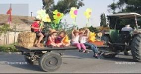 kids riding on a tractor holding large paper flowers
