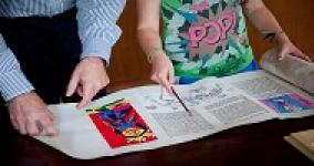 people reading megillah with colorful pictures in the scroll
