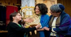 two women holding Torah while young girl holds the bottom of the Torah and smiles at the women