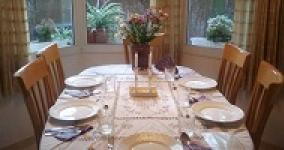 shabbat table set with plates, white tablecloth and candles