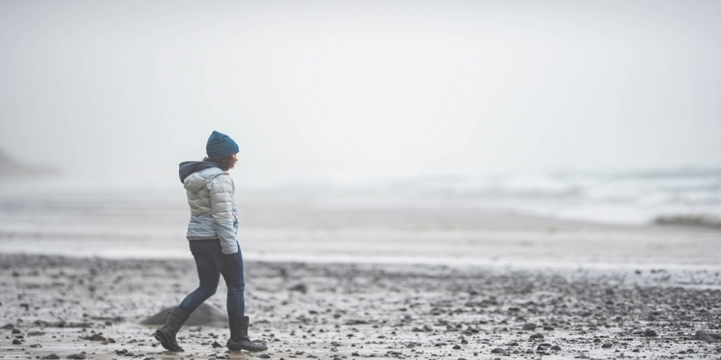 person walking on a rocky beach wearing winter clothes