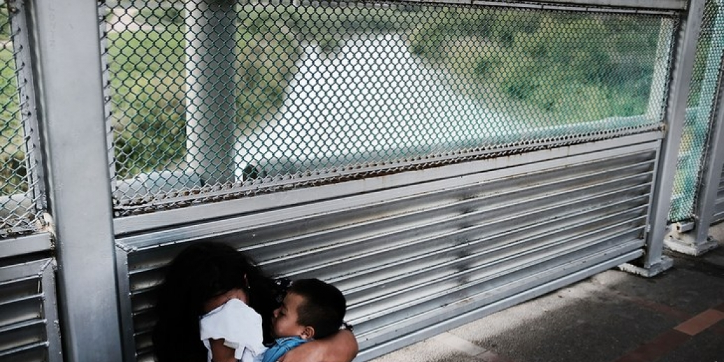 Photo of mother covering her face with a cloth, clutching a child, next to a fence, with a river in the background