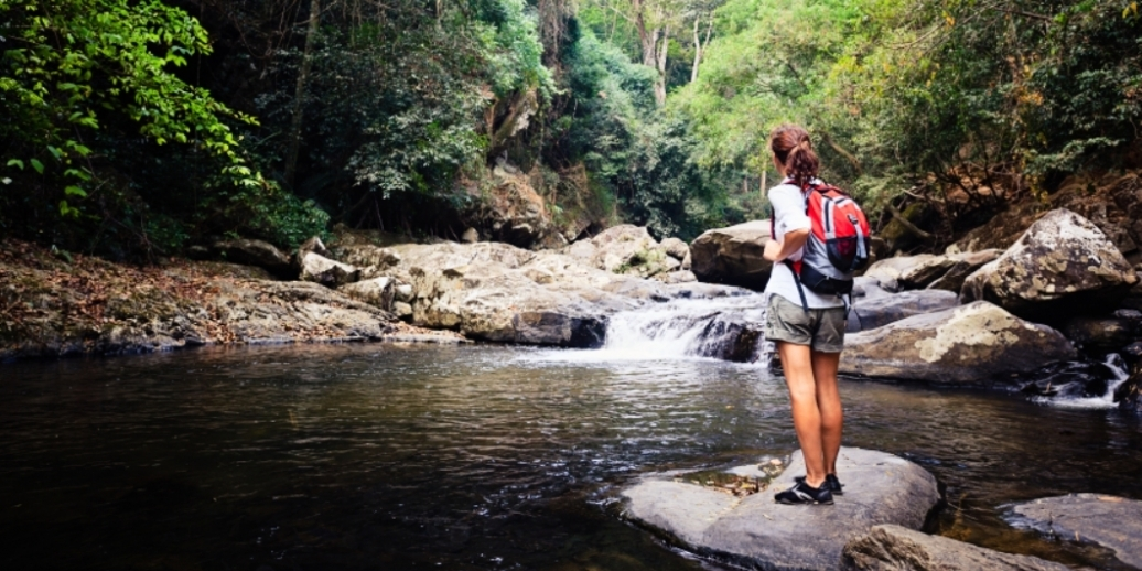 Woman hiking in forest stopping by a stream