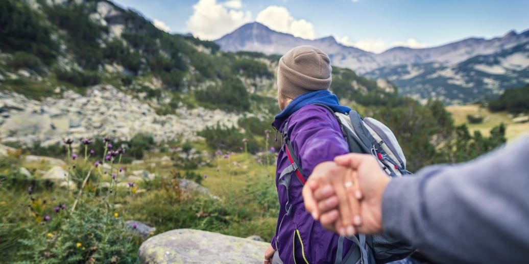 Woman holding hand of friend on hike