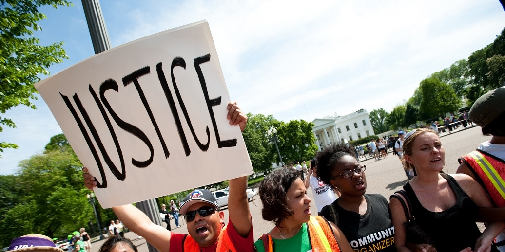 Person holding sign that reads Justice during protest