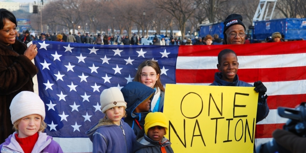 Children standing in front of American flag with sign that reads One Nation