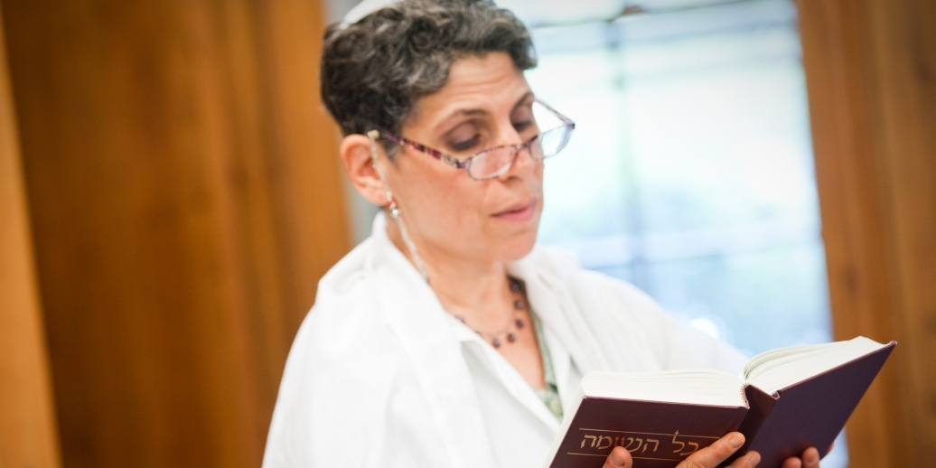 woman in white reading siddur