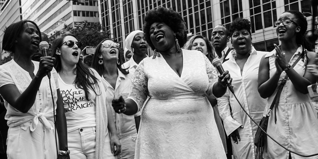 Resistance Revival Chorus singers wearing white and singing in the streets