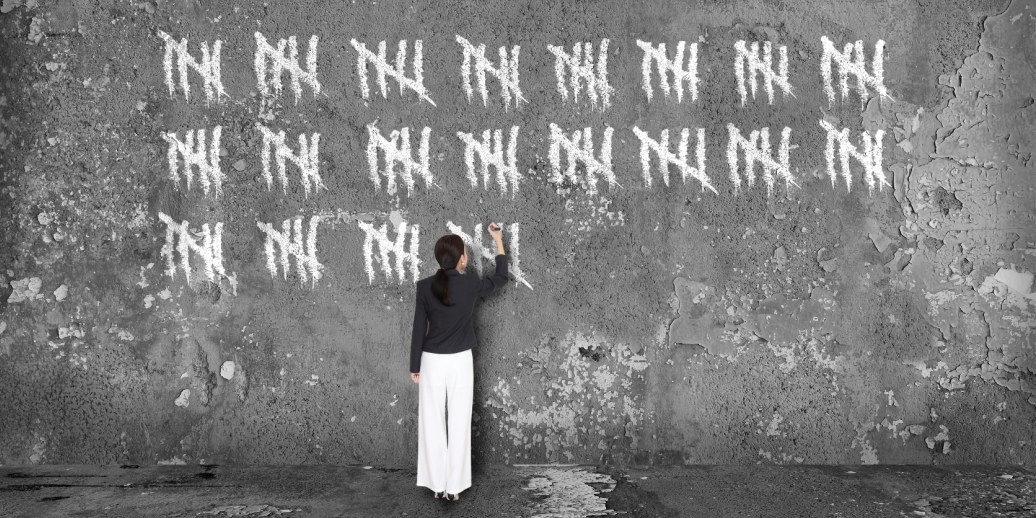 woman counting with chalk on a wall