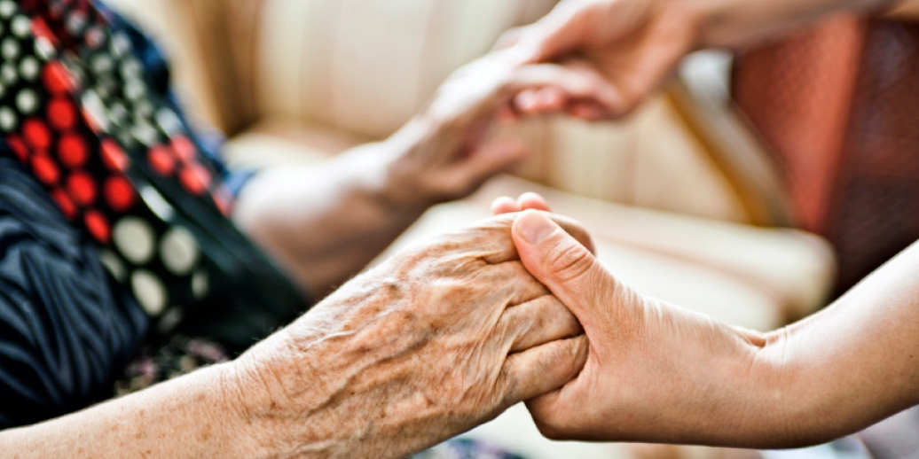 close up of young hands holding elderly hands
