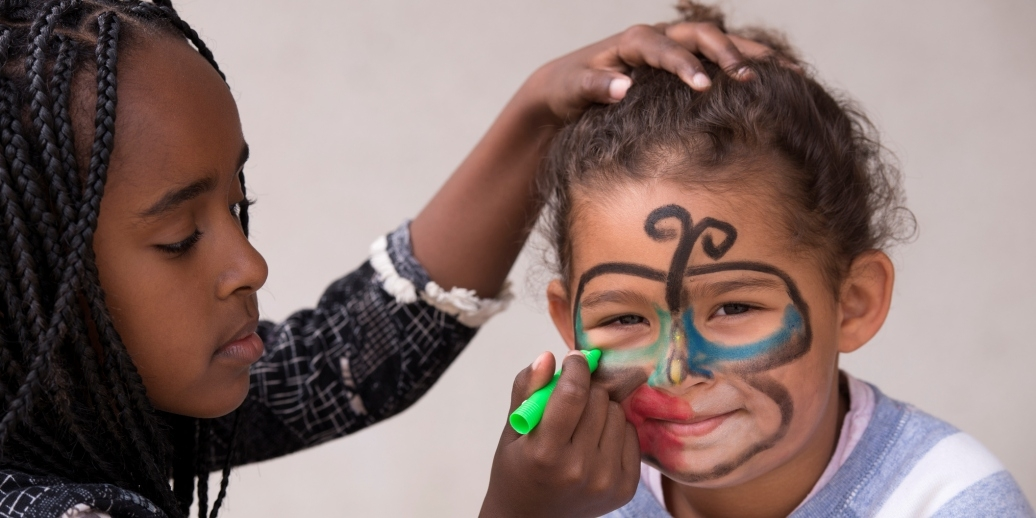 black girl drawing mask on the face of younger black child