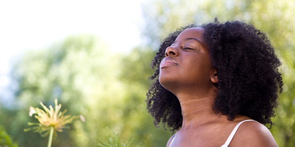 black woman inhaling deeply outdoors with greenery in the background
