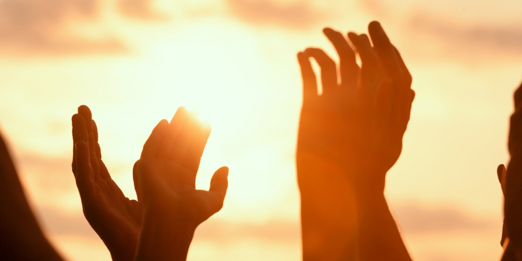silhouette of hands raised to sunlit sky