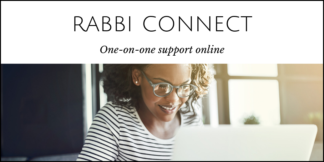 black woman wearing glasses smiling as she chats with someone on her laptop
