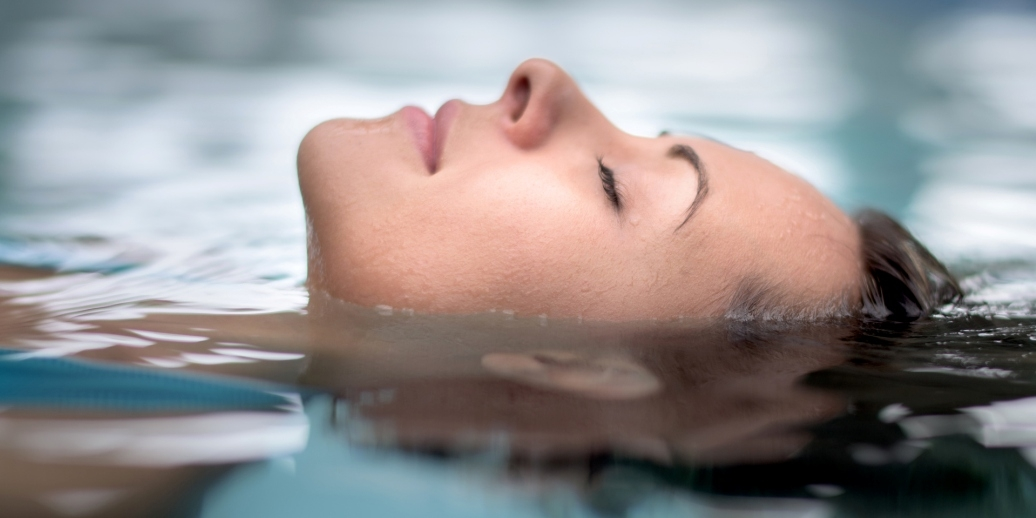 close up of woman's face floating peacefully in water