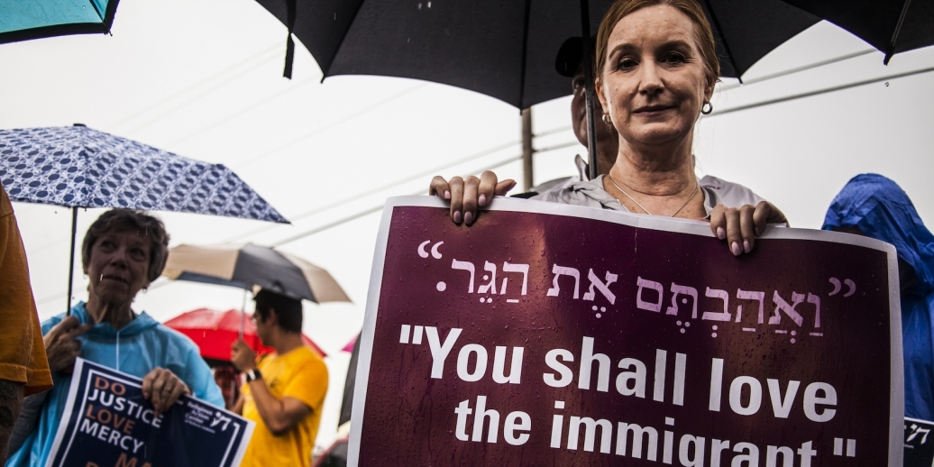 "woman holding sign ""you shall love the immigrant"""