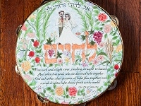 tambourine of bride and groom standing on the word l'chaim with a quote from the Baal Shem Tov.